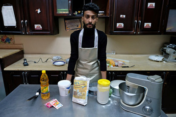 Nabil Al-Darsi, 29, an economics department graduate, poses for photo as he works at the kitchen after the baking courses in preparing cakes and sweets at Sarah Center for Sweets in Benghazi