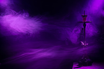 The classic hookah. Beautiful background, with colored rays of light and smoke. The concept of hookah Smoking.