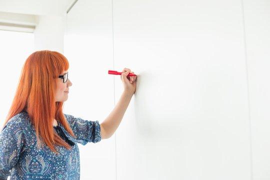 Businesswomen writing on whiteboard in creative office