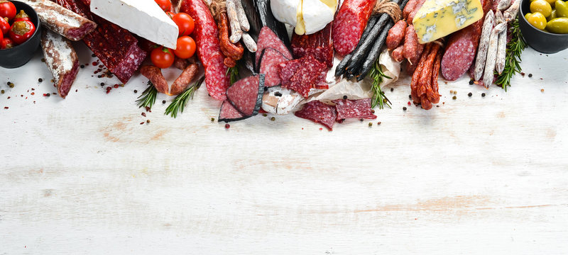 Assortment of cheese, dried salami and smoked sausages on a white wooden background. Top view. Free space for your text.
