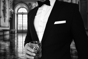 A close up view of a man in a black tuxedo holding a whiskey glass in a mansion. Great for use for a themed black tie event such as gatsbys mansion