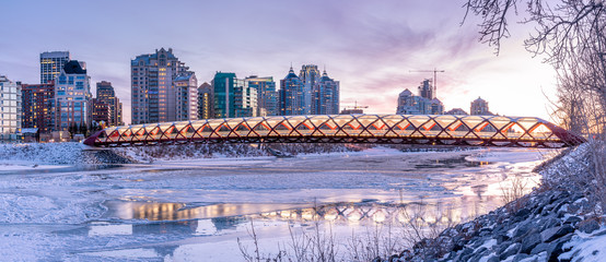 Evening skyline view along the Bow River in Calgary, Alberta.  Peace Bridge visible.