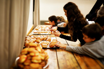 Children grab sufganiyot, deep-fried doughnuts eaten during Hanukkah, the 8-day Jewish Festival of Lights, as they mark the holiday in Kibbutz Tzuba