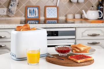 White toaster, glass of orange juice, slices of toasted bread, crispy toast with raspberry jam and bowl with confiture on wooden board. Served table for delicious meal. Fresh breakfast concept.