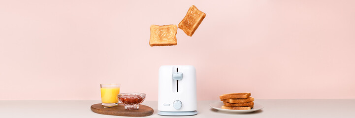 Toasted bread flew out of white toaster. Near glass of orange juice, bowl with strawberry jam and stack of toasts. Levitation food. Flat lay. Delicious breakfast concept. Copy space. Pink background.