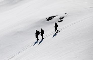 Three trekkers on a snowy slope
