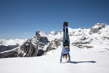 A woman doing a handstand in the mountains.