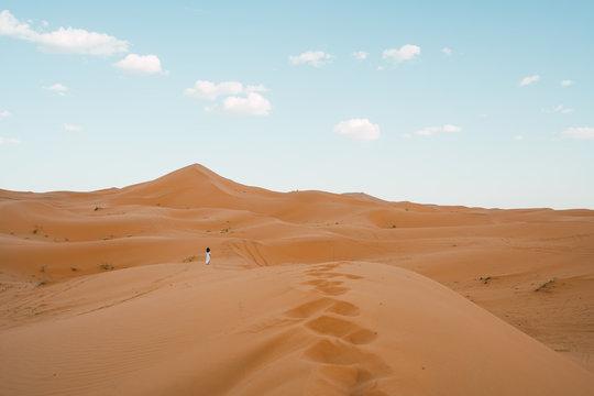 woman standing in sandy dunes in desert