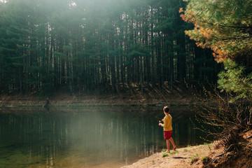 stock photo of boy fishing in beautiful emerald lake