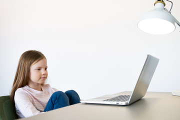 Cute little girl smiling and looking at laptop,Little girl using laptop
