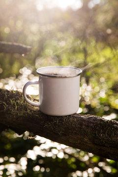 Blank white enamel coffee mug in the forest