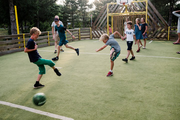 group of kids and two dad playing soccer