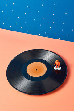 Plastic toy of astronaut on a vinyl record on a duotone stars background.