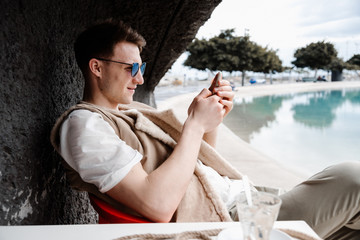 Young male browsing smartphone on beach