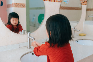 Asian little girl washes hands