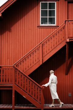 Young woman standing near stairs of cottage