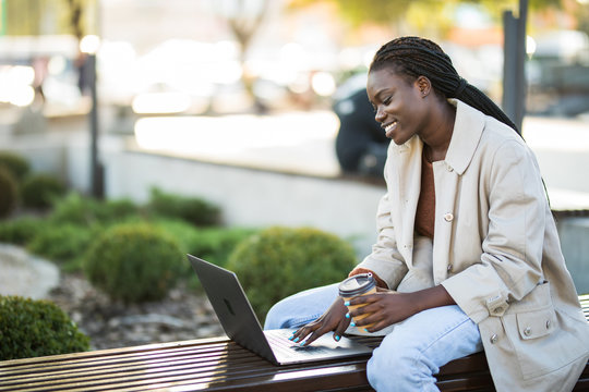 Young african woman in park. Beautiful woman sitting on bench drinking coffee and using laptop via airpods.