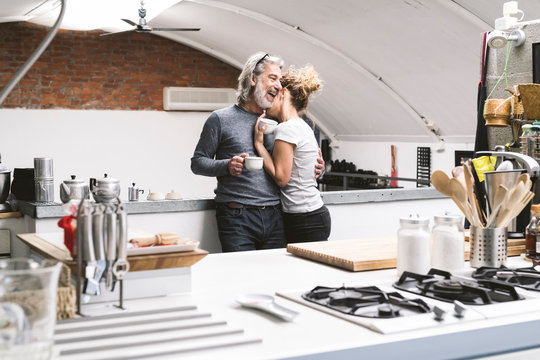Affectionate couple together in the kitchen at home