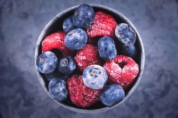 Top view of mixed blueberry and raspberry fruits in iron cup