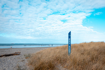 Beach sign on a background of sea and sky
