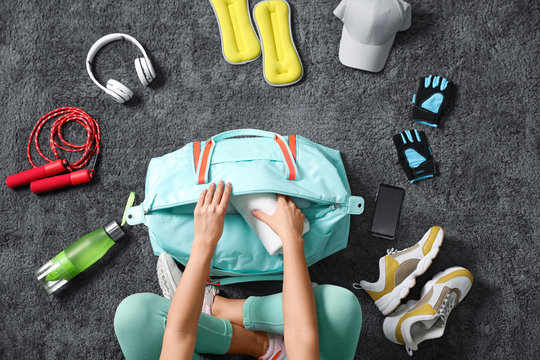 Woman with bag and sports items on grey carpet, top view
