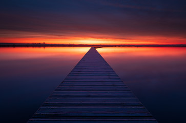 Very colorful and tranquil dawn at a jetty in a lake. Groningen, Holland.