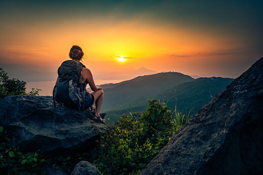 Young woman admire beautiful sunset over The Da Nang Bay and Ba Na mountains from the viewpoint, Vietnam