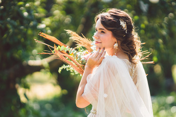 Beautiful bride with bouquet flowers stands on forest background. Rustic style. beautiful bride in...