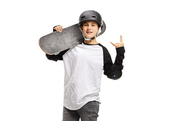 Kid posing with a skateboard and gesturing rock and roll sign