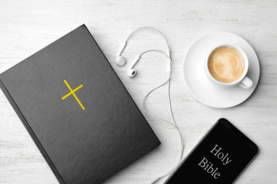 Bible, phone, cup of coffee and earphones on white wooden background, flat lay. Religious audiobook