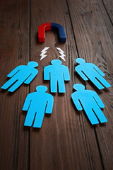 Magnet attracting paper people on wooden background