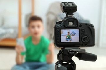Cute little blogger with phone and selfie stick recording video at home, focus on camera Fototapete