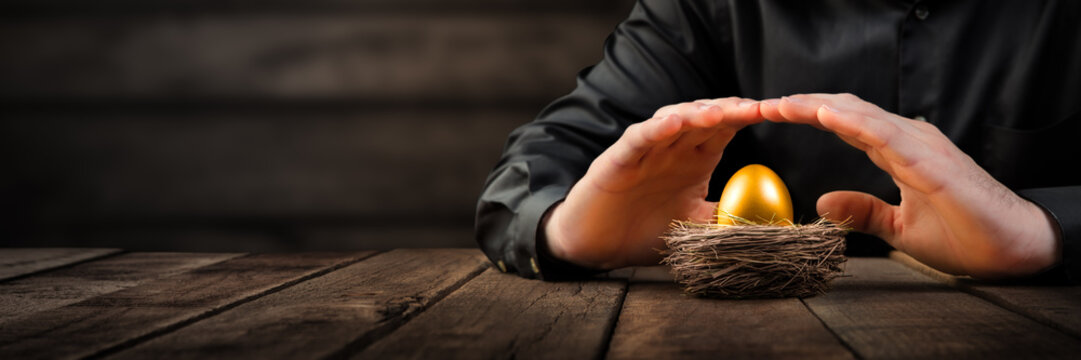 Protecting Hands Over Golden Nest Egg On Wooden Table - Investment Protection Concept