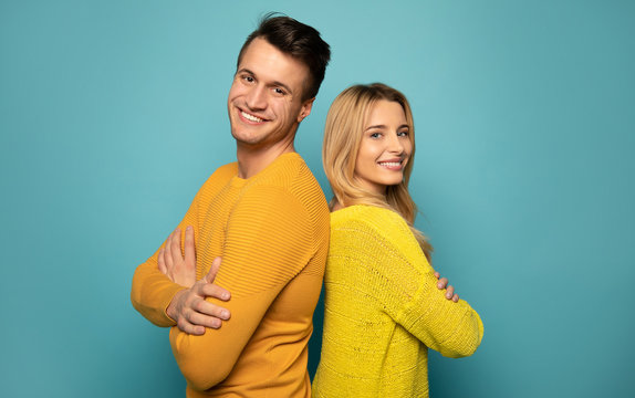 Partners in whole life. Handsome man and alluring girl are standing back to back, posing together in profile, looking in the camera and smiling sincerely.