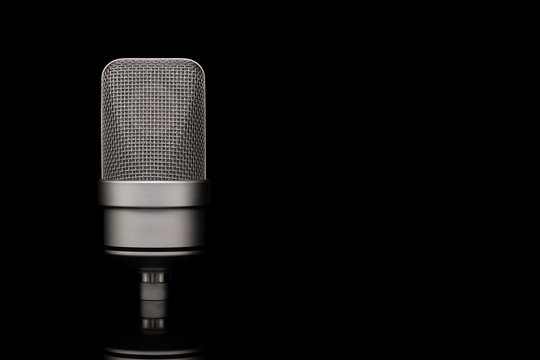 Mic - Close-up of professional condenser microphone on a black isolated background