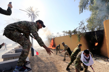 Hashd al-Shaabi fighters set fire on the U.S. Embassy wall to condemn air strikes on their bases, in Baghdad