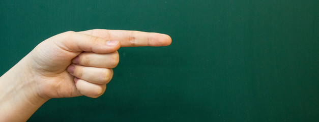 The hand of a teenager with an outstretched index finger on the background of a green chalkboard Wall mural