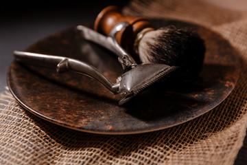 herramientas de tienda de barbería, utensilios de barbero. como una brocha de afeitar, navaja de afeitado y maquina de afeitar manual antigua. sobre un plato, tela de saco y suelo de pizarra. foto de