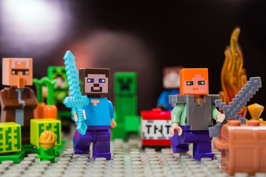 Kiev, Ukraine - January 30, 2019: Minifigure Steve with diamond sword and Alex run away from the Creeper. Characters of the game Minecraft.