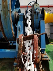 White painted anchor windlass chain on a anchor handling tug boat