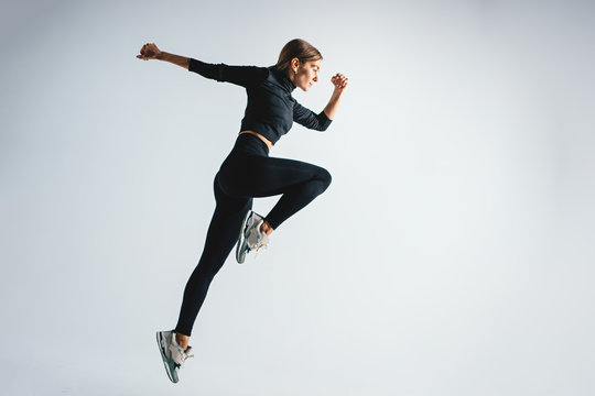 Sporty charismatic woman jumping and running against white color background. Young athletic girl in jump moment in studio