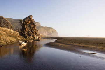 Rock formations, black sand, river and mountains of Karekare Beach in West Auckland, New Zealand.