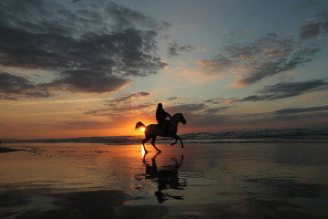 A Palestinian man rides a horse on a beach during the last sunset of 2019, in Gaza City