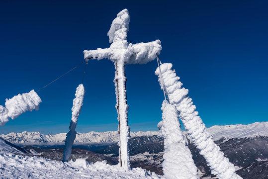 cross in snow at the nösslachjoch peak in tyrol, austria