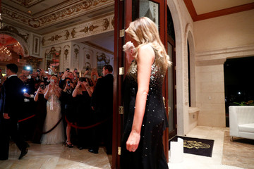 Guests take photos as U.S. President Donald Trump accompanied by first lady Melania Trump arrive at the Mar-a-Lago resort in Palm Beach