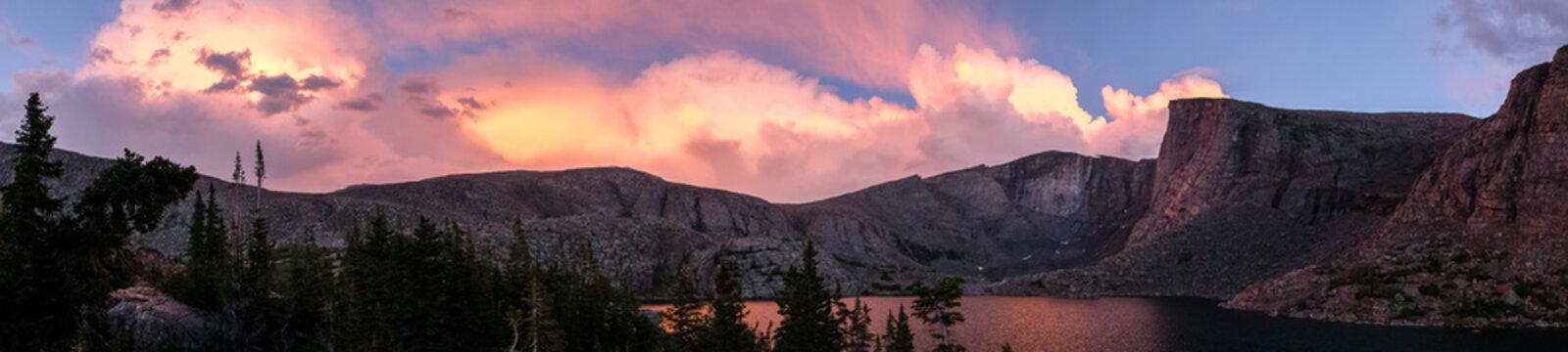 Panorama of pink sunset on mountain lake