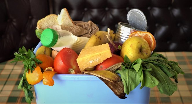 Household food waste. Uneaten spoiled foods in bin: bread, bakery, vegetables, fruits milk. Families throw away meals