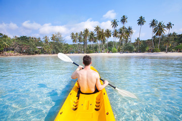 kayaking on tropical beach, travel to Asia, summer holidays, tourist paddling on kayak in turquoise sea water