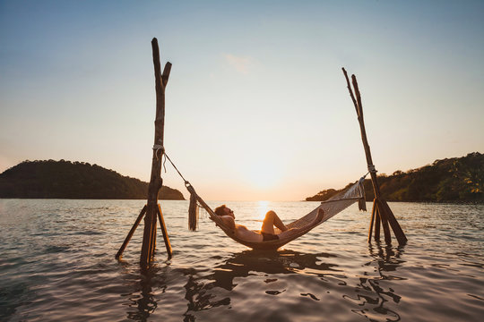 beach getaway, relaxation in hammock at sunset, paradise remote island holidays, happy man tourist resting and enjoying life