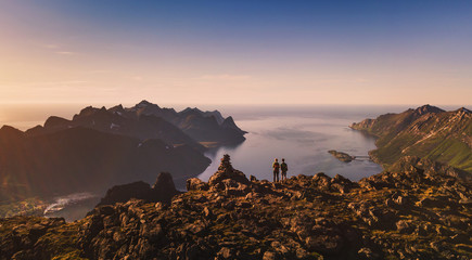travel and adventure banner background, couple of travelers backpackers standing on top of the mountain in Senja, Norway